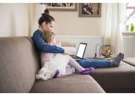 一位母亲和女儿坐在一起使用笔记本电脑的侧_2627520