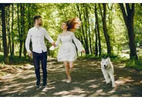 一位穿着白色连衣裙的浅发女孩正和她的狗和_2611529