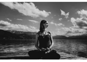 一位身着黑衣的漂亮孕妇坐在湖上的木桥上_2913958