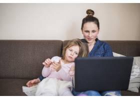 一名妇女与女儿坐在一起使用笔记本电脑的肖_2627508