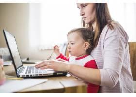 一名妇女和她的孩子在木桌上使用笔记本电脑_2610751
