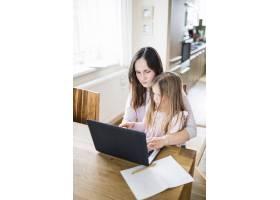 一名妇女带着女儿在家用笔记本电脑工作_2610746