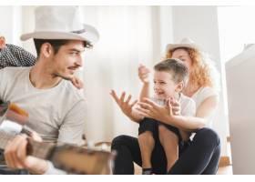 一名男子与家人坐在一起弹吉他_3143594