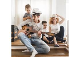 一名男子在家里为家人弹吉他_3143585