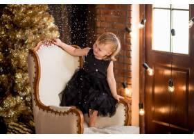 穿着黑色连衣裙的小女孩坐在圣诞装饰品之间_2631512