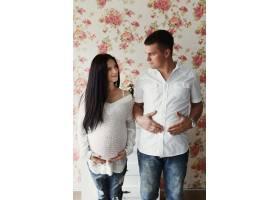 站在花墙前的男子和孕妇双手放在肚子上_1620791