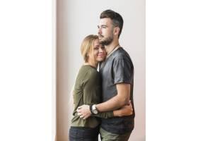 米色背景下微笑的年轻女子拥抱她的男朋友_2718742