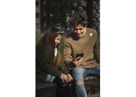 美丽的微笑女孩坐在公园里父亲拿着手机_2573038