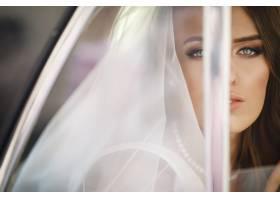 美女新娘坐在复古车里捧着结婚花束玩得开心_2612758