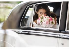 美女新娘坐在复古车里捧着结婚花束玩得开心_2612762