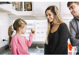 高兴的父母看着他们的女儿在厨房里拿着纸杯_2886710