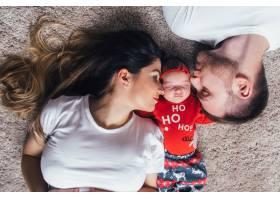 漂亮的父母带着女儿躺在地板上_2437581