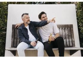 父子俩坐在长凳上喝啤酒_2303205