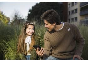 幸福的父女看着对方手里拿着手机_2573006