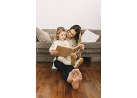 微笑的女人在沙发附近给女儿读书_2925015