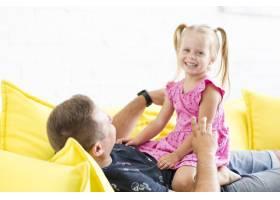 微笑的女孩和她的父亲坐在沙发上的肖像_2667026