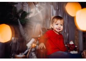 微笑的小女孩坐在架子上漂亮的圣诞装饰品之_2437946