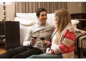 微笑的年轻夫妇在客厅里拿着酒杯_3165854