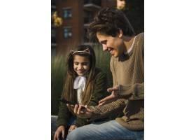 微笑的父女看智能手机的特写_2573016