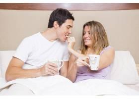 快乐的女人给坐在床上的男朋友喂饼干_3157164