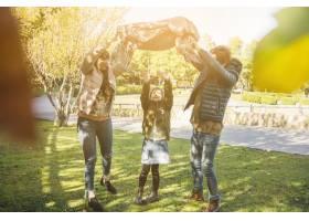 快乐的女孩和她的父母在公园里享受周末_2586860