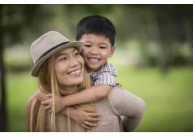 快乐的年轻母子俩笑着让小男孩骑在她背上_3175256