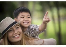 快乐的年轻母子俩笑着让小男孩骑在她背上_3175258