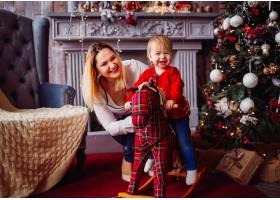快乐的母亲和可爱的孩子在玩具马上在圣诞树_2437944