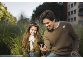 快乐的父亲用手机给女儿看东西_2573000