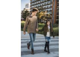 快乐的男人和他的女儿一起走在人行道上_2573077