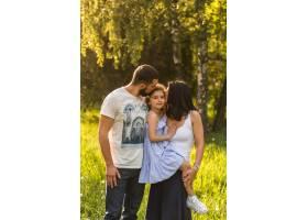 慈爱的父母在公园亲吻他们的女儿_2586765