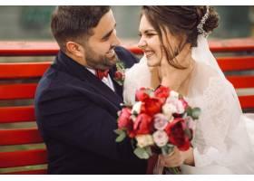 新娘和新郎在外面的长椅上拥抱亲吻玩得很_2612628