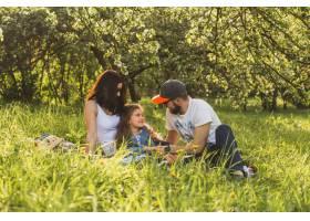 欢快的一家人坐在绿色公园的草地上_2572812