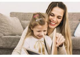 欢快的母女俩在沙发旁看书_2848766