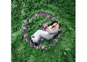 新婚夫妇躺在绿色草坪上紫丁香的圆圈里_1620882