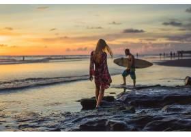 日落时海滩上的人们那个女孩在落日的背景_3064207