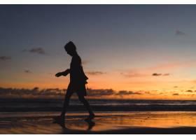 日落时海滩上的人们那个女孩在落日的背景_3064231