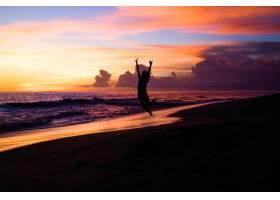 日落时海滩上的人们那个女孩在跳_2440501