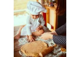 母亲带着儿子在厨房里揉面团_2437760