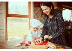 母亲带着儿子在厨房里揉面团_2437763