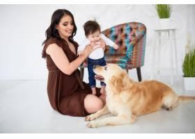 母亲带着女儿坐在地板上看着狗_2437826