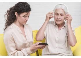 女儿看手机母亲戴着耳机听音乐_2690822