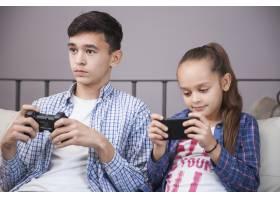 女孩拿着控制器在青少年附近使用智能手机_2041321