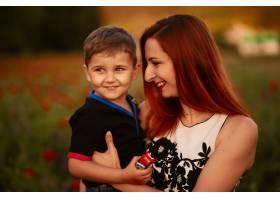 妈妈抱着可爱的小儿子站在绿地上手里拿着_2914002