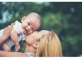 妈妈抱着宝宝在公园里欢笑嬉戏_2523612