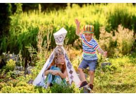 孩子们像美国原住民一样在田野上的绿草地上_2612640