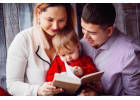 小女孩和爸爸妈妈坐在一起看书_2437938