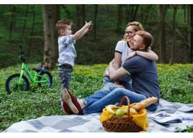 小男孩在公园野餐时用智能手机给父母拍照_2438059