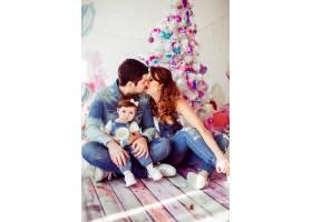 父母与小女儿坐在明亮的圣诞树前亲吻_1617236