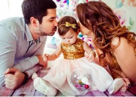 父母亲吻穿着金色连衣裙的小女孩_1617241